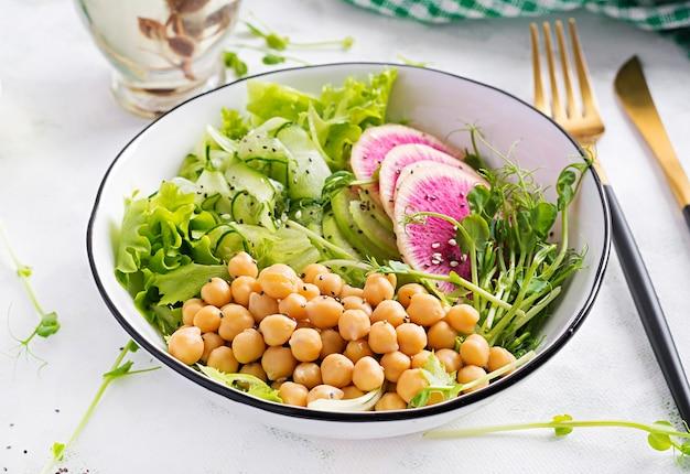 트렌디 한 샐러드. 병아리 콩, 수박 무, 오이, 완두콩 콩나물을 곁들인 채식주의 부처 그릇. 건강한 균형 잡힌 식사.