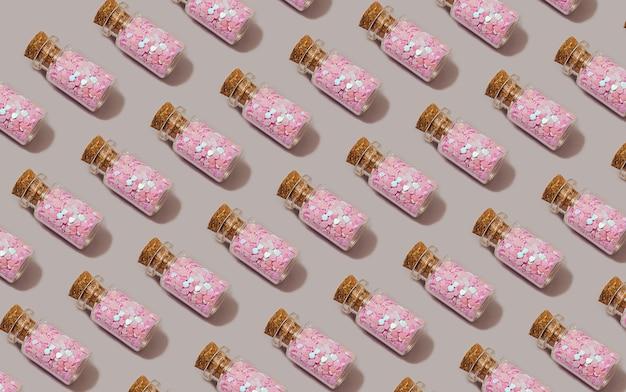 Модный бесшовный образец из розовых стеклянных бутылок с блеском на пастельно-сером и фиолетовом фоне. рождество, праздник и вечеринка фон.