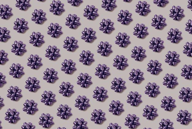 Trendy seamless pattern made with purple holiday wrap bow and ribbon on a gray background. christmas and party backdrop.