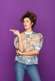 明るい紫色の背景から離れている携帯電話を持つトレンディな自己保証の女性