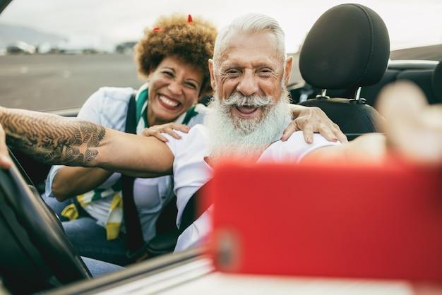 夏休みにコンバーチブルカーで楽しんでいるトレンディな年配のカップル-携帯電話で屋外のカブリオレで自分撮りをしているうれしそうな高齢者