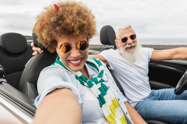 Trendy senior couple having fun taking a selfie with mobile phone in convertible car during summer vacation - focus on mature woman face