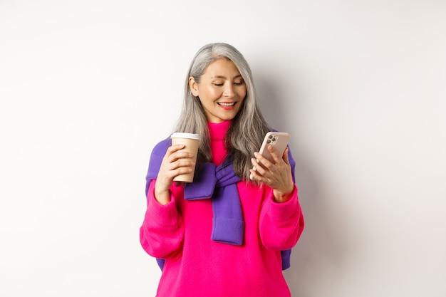 Модная старшая женщина пьет кофе и с помощью смартфона. корейская старшая дама читает сообщение на мобильном телефоне и улыбается, белый фон.