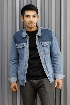 Trendy sexy asian man in denim jacket standing against white colored wall. medium shot vertical portrait, fashionable urban concept.