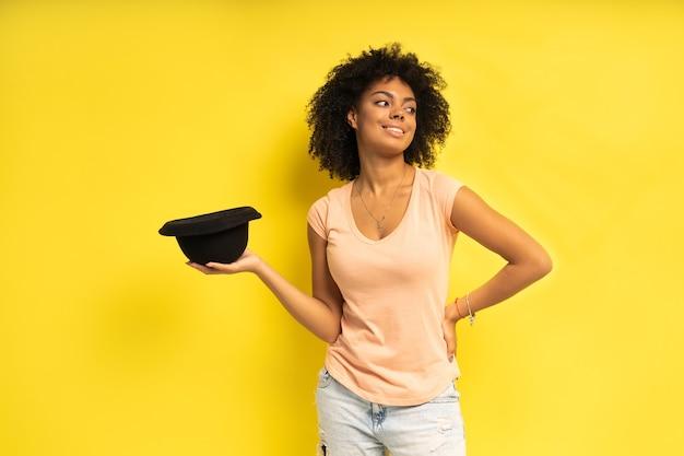 黄色の背景の上にポーズをとってカジュアルな服を着て黒い帽子のトレンディなセクシーな若い女性