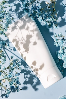 Trendy shot of unbranded white plastic tube with hand or face cream, or face mask or skrub. beauty care package with blue flowers of gypsophila