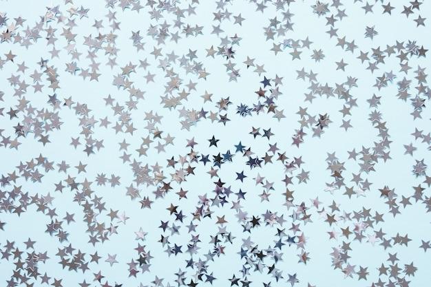 青の背景にトレンディな銀箔紙吹雪星