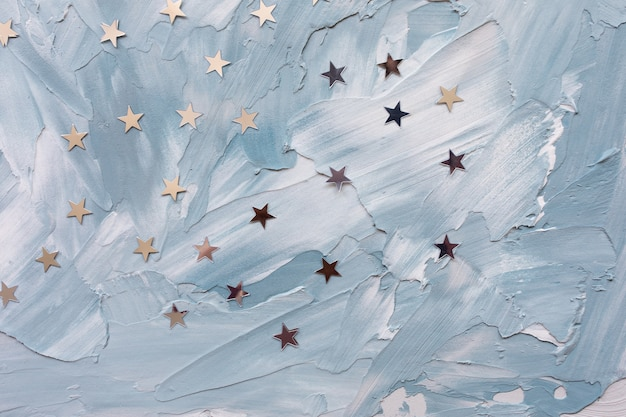 Trendy silver foil confetti stars on white and blue background.