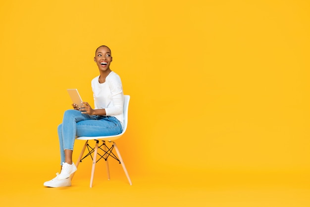 Trendy smiling african american woman sitting on a chair using tablet computer thinking and looking at empty space aside isolated yellow wall