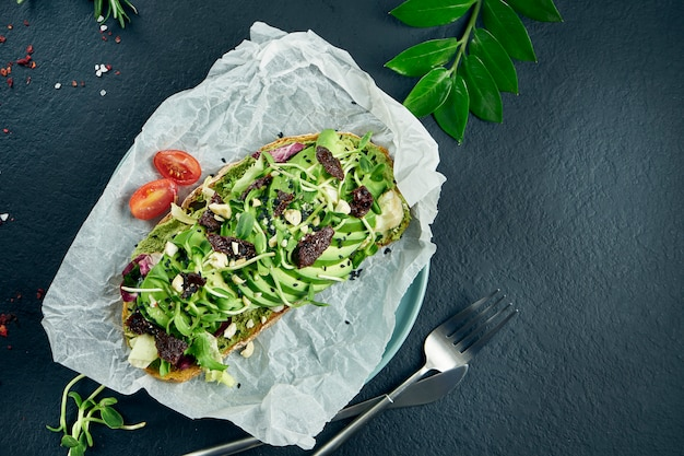 Trendy street food snack. tasty avocado toast on craft paper on a black table. food flat lay, copy space. vegetarian nutrition. top view