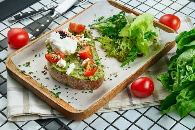 Trendy street food snack. tasty avocado toast on craft paper on a white table. food flat lay, copy space. vegetarian nutrition. close up view