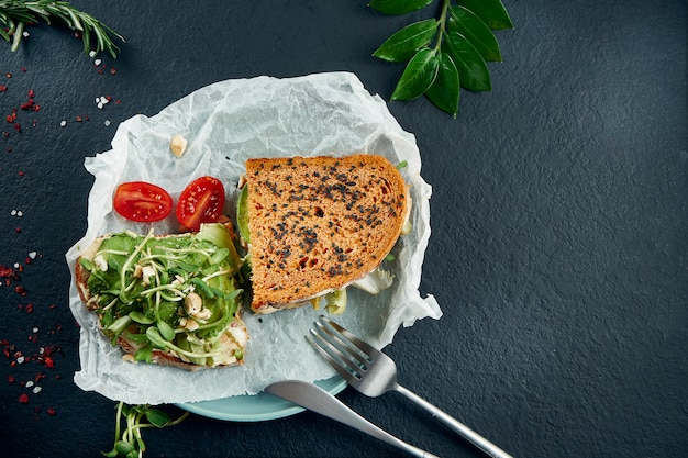 Trendy street snack. tasty sandwich toast with avocado and hummus and microgreen on craft paper on a black slate table. top view. food flat lay with copy space