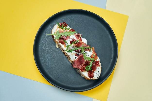 Trendy street snack. tasty sandwich with jamon, poached eggs, cucumber and microgreen on black plate on colored surface copy space.