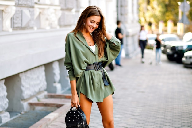 Trendy street style image of amazing fashionable young pretty woman posing on the street