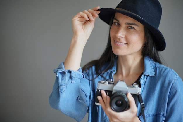 Trendy stunning brunette with vintage camera