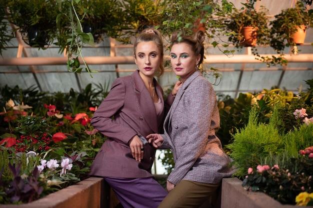 トレンディなスタイル。スタイリッシュなジャケットを着て一緒に座っている魅力的な愉快な女性