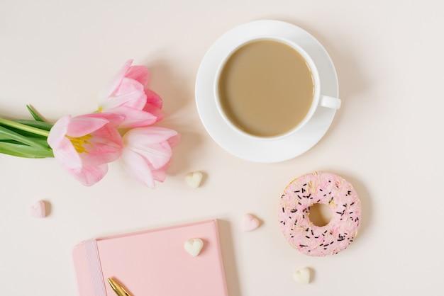 Модный стильный концепт для блогера-фрилансера: розовый дневник, блокнот, донат, розовые тюльпаны и чашка кофе на бежевом фоне. работа из дома