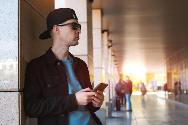 스마트 폰 헤드폰 도시 도시 일몰 유행 세련된 남자 검은 모자 선글라스. 사람, 음악, 기술, 레저 라이프 스타일. 비즈니스 센터 터널 여유 공간 관점 햇빛