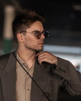 眼鏡をかけたファッショナブルな服で無精ひげと髪型を持つハンサムな若い男のモデルのトレンディなスタイリッシュな肖像画。