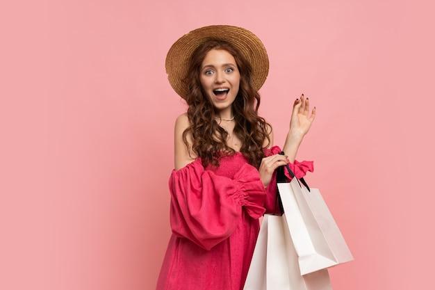 Модная стильная женщина радуется продажам, времени покупок, изолированному на розовой повседневной одежде.