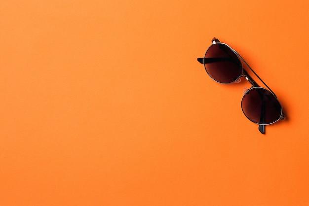 Модные солнцезащитные очки, изолированные на оранжевом фоне.