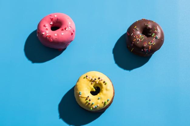 Trendy sunlight. summer doughnuts on bright light blue turquoise background. minimal summer concept. pop art style. donut