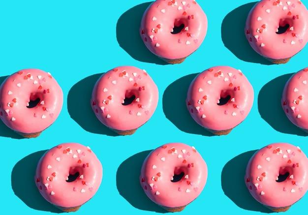 트렌디한 햇빛. 밝은 파란색 청록색 배경에 분홍색 도넛으로 만든 여름 패턴입니다. 최소한의 여름 개념입니다. 팝 아트 스타일입니다. 도넛