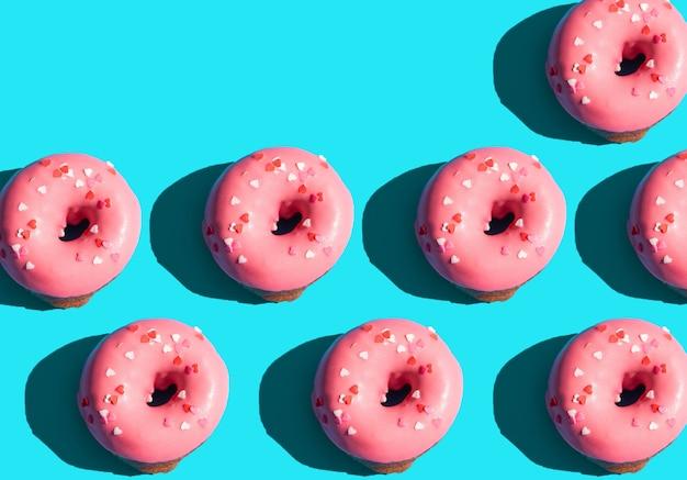 트렌디한 햇빛. 밝은 파란색 청록색 배경에 분홍색 도넛으로 만든 여름 패턴입니다. 최소한의 여름 개념입니다. 팝 아트 스타일입니다.