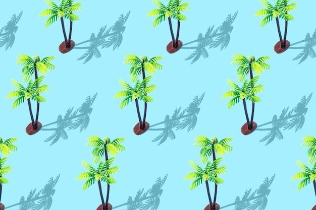 Ультрамодный солнечный летний образец с игрушкой тропической пальмы на пастельно-синем фоне.