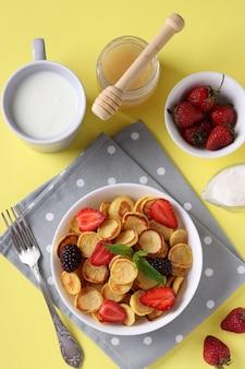 イチゴ、ブラックベリー、黄色の背景に白いボウルに蜂蜜と朝食のトレンディな小さなパンケーキ。