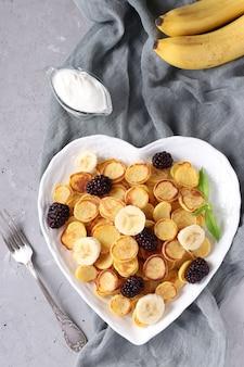 Модные крошечные блинчики с ежевикой и бананом в тарелке в форме сердца