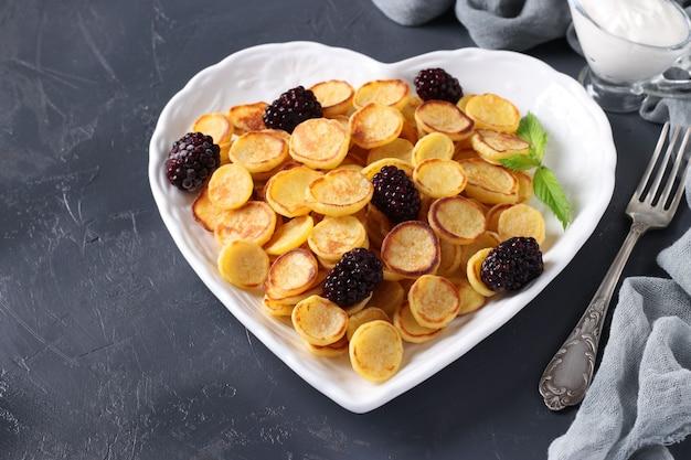 Модные крошечные блины с ежевикой в тарелке в форме сердца на темном фоне, крупным планом
