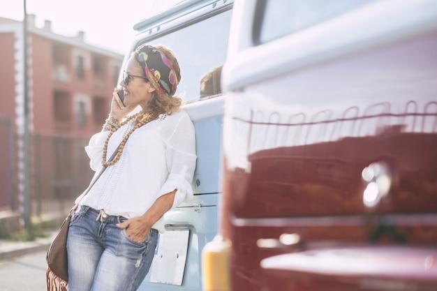 トレンディな旅行者の若い女性が笑顔で電話で話します-駐車場の車とアウトドアシティのレジャー活動を一人で楽しんでいる現代のファッションの女性