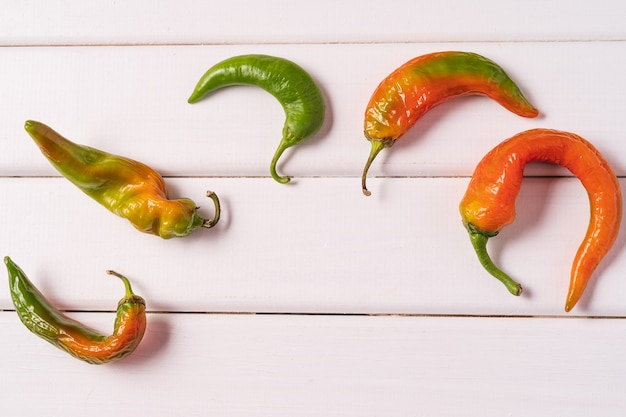 Trendy ugly curved bent peppers on white wooden background.