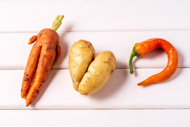 Trendy ugly curved carrot, pepper and potato on white wooden background.
