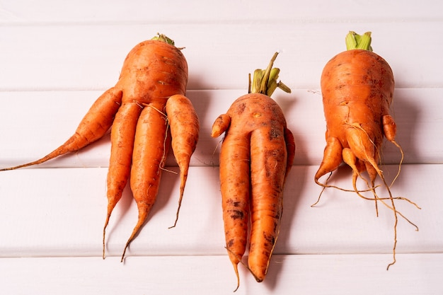 Trendy ugly curved carrots on white wooden background.