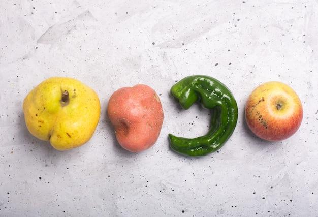 Модные уродливые органические фрукты и овощи на столе
