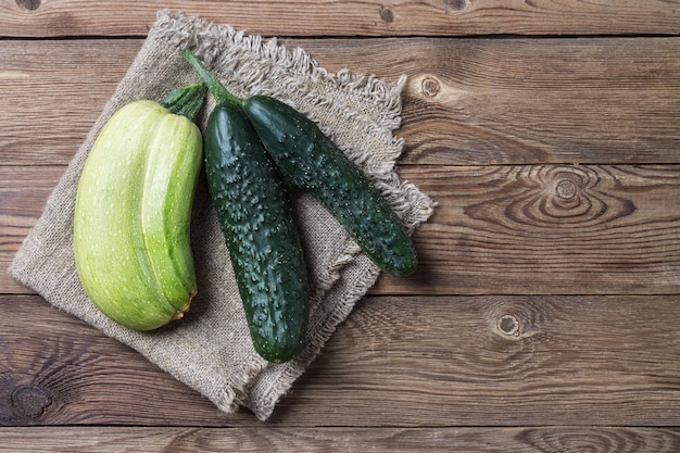 Trendy ugly organic natural cucumber and squash on napkin, on natural wooden table. copy space.