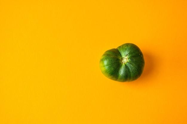 트렌디한 못생긴 유기농 야채. 노란색 바탕에 녹색 토마토입니다. 못생긴 음식 개념 요리. 평면도. 텍스트를 위한 공간을 복사합니다.
