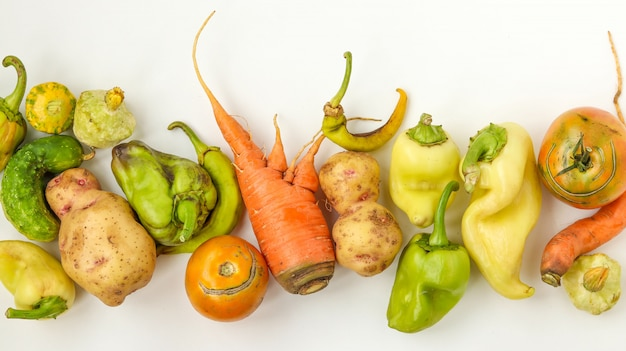 Trendy ugly vegetables: potatoes, carrots, cucumber, peppers and tomatoes on white