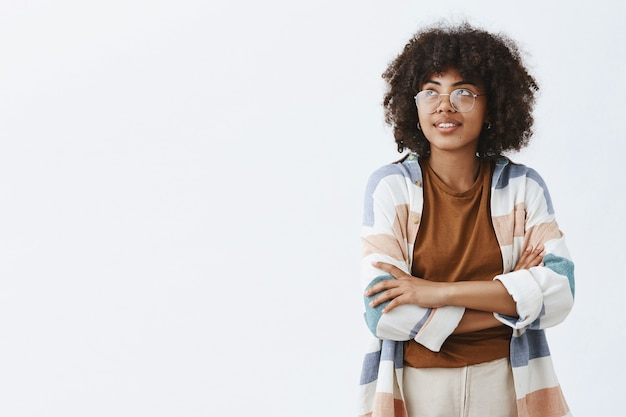 Trendy urban african american female employee in transparent trendy glasses and outfit holding hands crossed on chest and gazing at upper left corner with dreamy cute smile