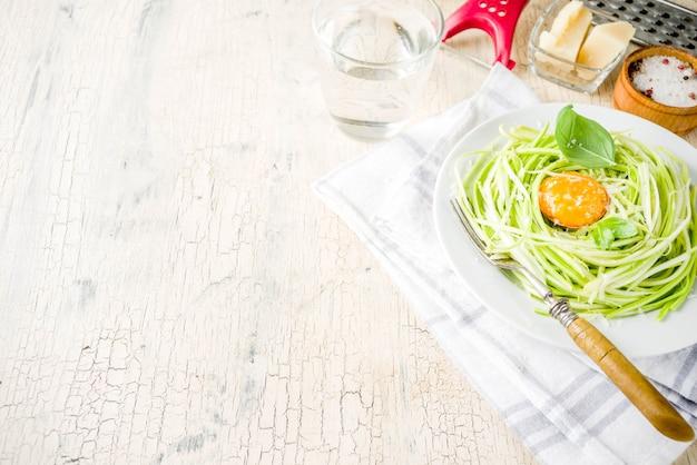 トレンディなビーガンフードレシピ、チーズズッキーニスパゲッティパスタ、卵黄とパルメザンチーズ、オリーブオイル、バジルの葉、明るいコンクリート背景