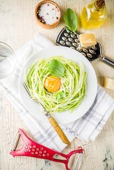 トレンディなビーガンフードレシピ、チーズズッキーニスパゲッティパスタ、卵黄、パルメザンチーズ、オリーブオイル、バジルの葉、軽いコンクリート表面