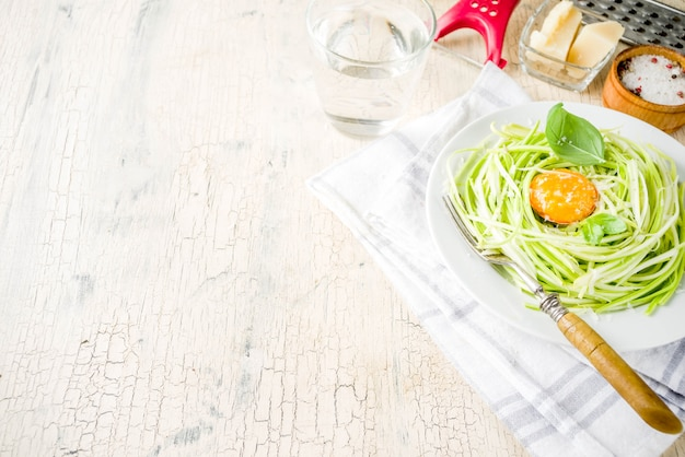 Trendy vegan food recipes, cheese zucchini spaghetti pasta with egg yolk with parmesan, olive oil and basil leaves, light concrete background