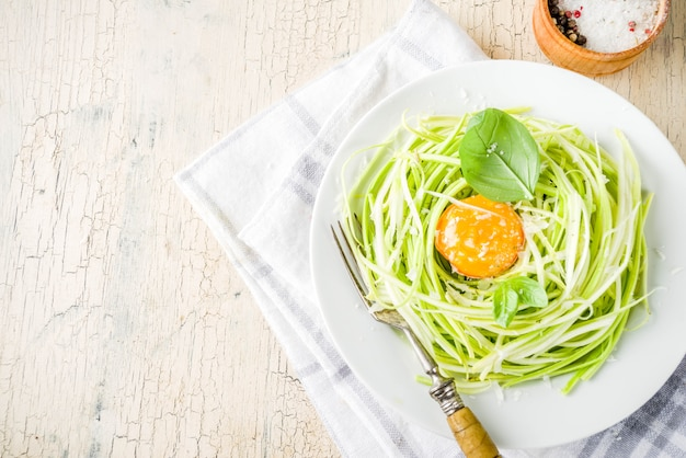 Trendy vegan food recipes, cheese zucchini spaghetti pasta with egg yolk with parmesan, olive oil and basil leaves, light concrete surface
