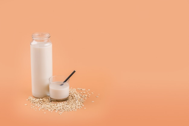 Trendy vegan non dairy alternative milk. oat milk in bottle and in a glass on the oat flake on pastel peach color background, copy space