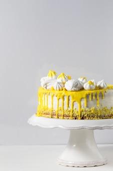 Модный белый торт с желтым шоколадным ганашем, зефиром и безе на подставке для торта