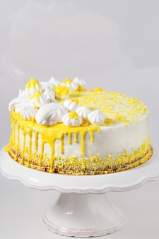 Trendy white cake with yellow chocolate ganache, marshmallow and meringues on a cake stand
