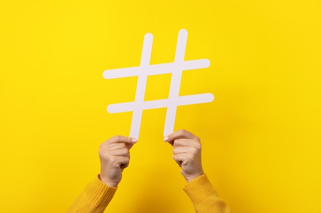 Trendy white hashtag in hands over yellow background