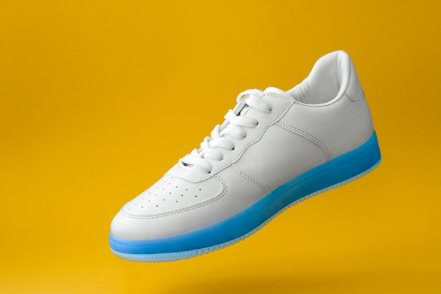 Trendy white sneakers with blue sole  isolated on yellow background